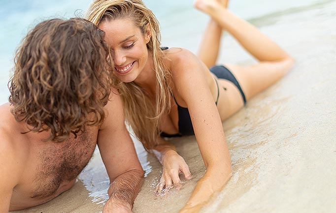 a man and woman laying on wet sand on the beach