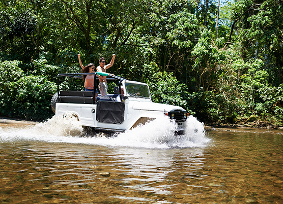 couple driving a white jeep through deep water in the foset