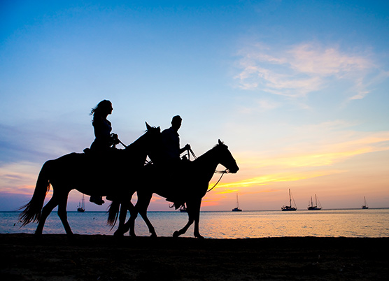 couple riding horses on the beach at sunset