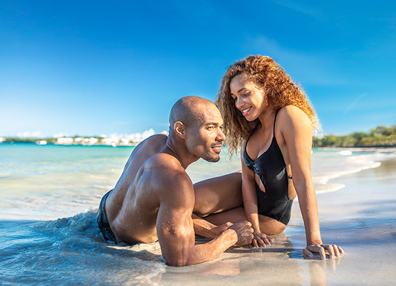 couple sitting in shallow ocean water on the beach