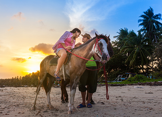 woman sitting on a horse talking to a man on the beach at sunset