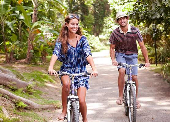 man and woman riding bikes on a path surrounded by trees