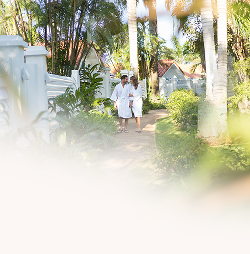 couple wearing robes walking on a sidewalk surrounded by greenery