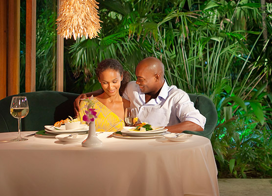 couple sitting on the same side of the table on a couch having dinner