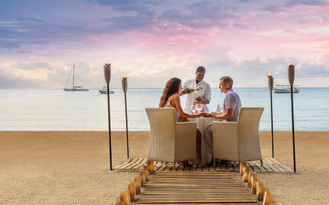 waitress pours champagne for a couple having a private dinner on the beach