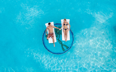 aerial view of a man and woman laying on white rafts in the pool