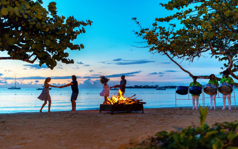 two couples dancing at a beach bonfire at sunset