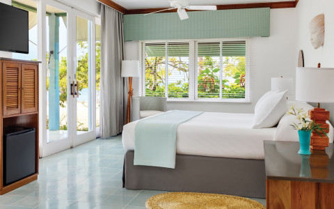 guest room with white sheets, light blue quilt, and double doors leading to a balcony