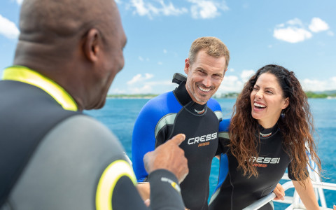 man talking to a couple wearing wetsuits about to go scuba diving