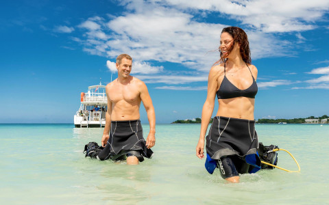couple with wetsuits half on walking in the water from a boat towards the shore