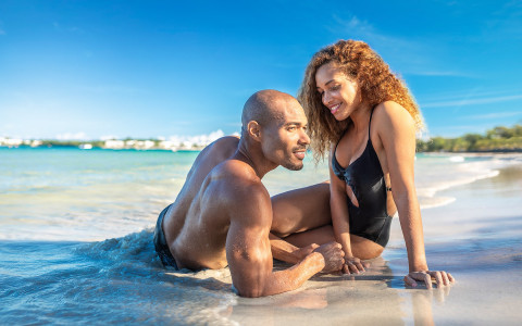 couple sitting in shallow beach water
