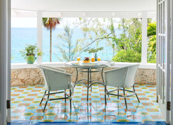 hibiscus cottage balcony with white whicker seating and colorful tile floors