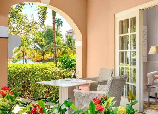 one bedroom beachfront suite entrance with whicker table
