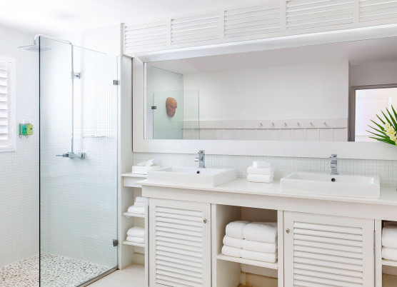 one bedroom beachfront suite bathroom with cabinets and furnishing and a glass walk in shower