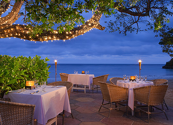 white table cloth covered tables on an outdoor patio overlooking the ocean