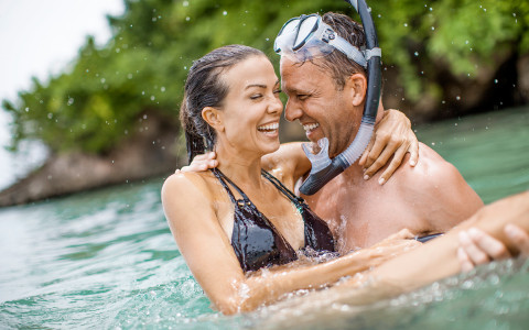 man wearing snorkeling headpiece holding a woman in the ocean water laughing