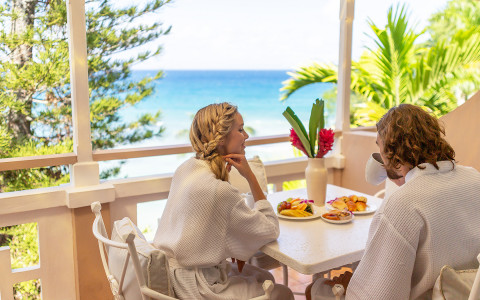 man and woman enjoying a breakfast while looking at ocean