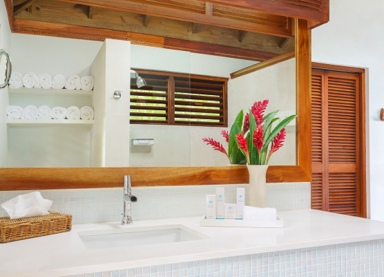 bathroom with wooden accents, white counters, sink, and decorative flowers