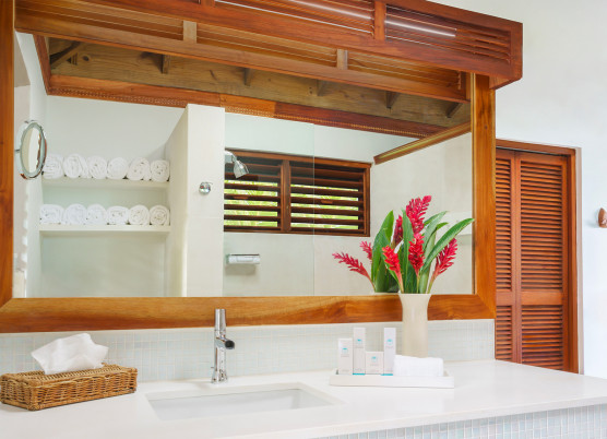 a bathroom with white marble sink and wood accents