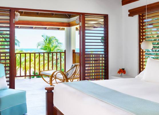 a bedroom with white linens and a balcony with a beach view