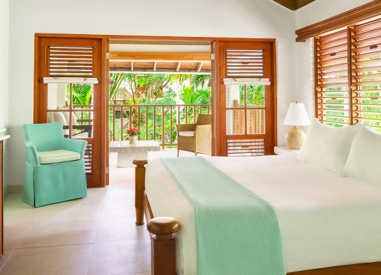 a bedroom with an open veranda and large bed with turquoise decor