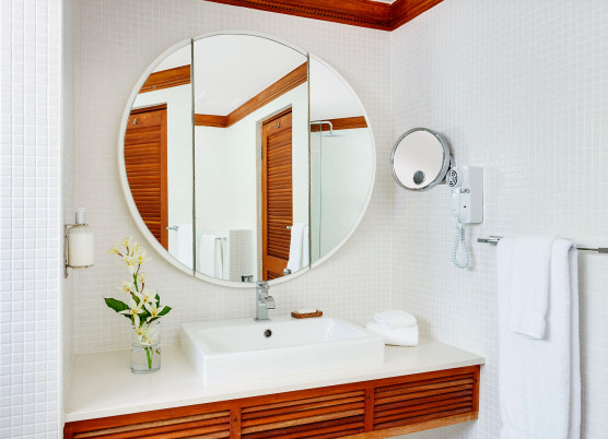 bathroom with round mirror and white marble sink