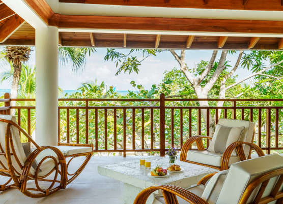 a patio with comfortable chairs overlooking trees with the ocean in the distance