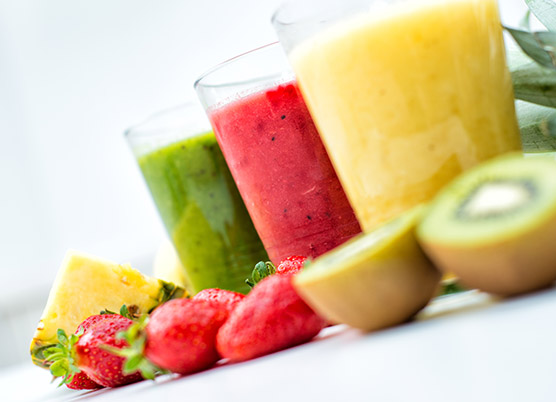 colorful juice drinks with fruit beside them
