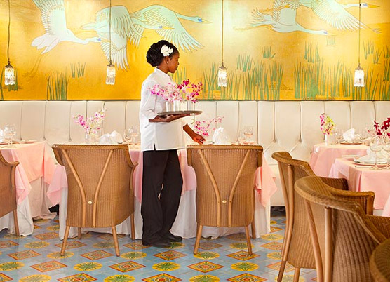 cocktail waitress carrying flower centerpieces for the restaurant