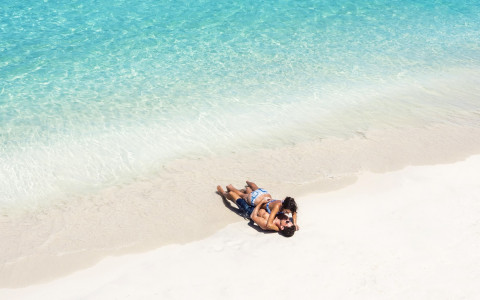 aerial view of a couple laying in the sand together near the water