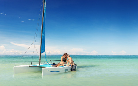 man and woman sitting on a small hobie cat boat in shallow ocean water near the show