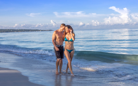man and woman in swimsuits walking along the beach