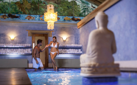 couple stepping into an indoor spa pool