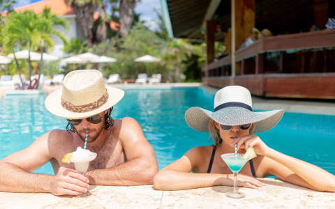 man and woman wearing wide brim hats standing in the pool with cocktails