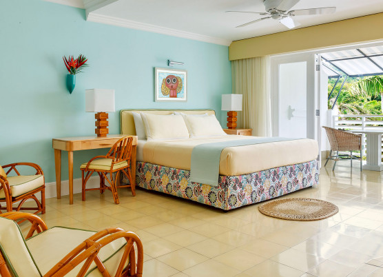 bedroom with light blue walls, light yellow linens and chairs, blue draped quilt, and balcony overlooking the ocean