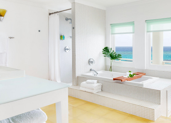 bathroom area with white tile tub and shower area, windows overlooking the ocean, and vanity area