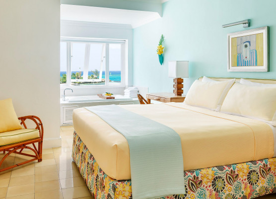 guest bed room with light yellow linens, light blue draped quilt, and yellow chair