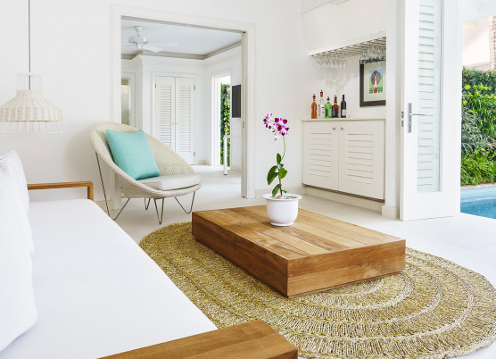 living room area with beach themed decor and doors open to the private pool area