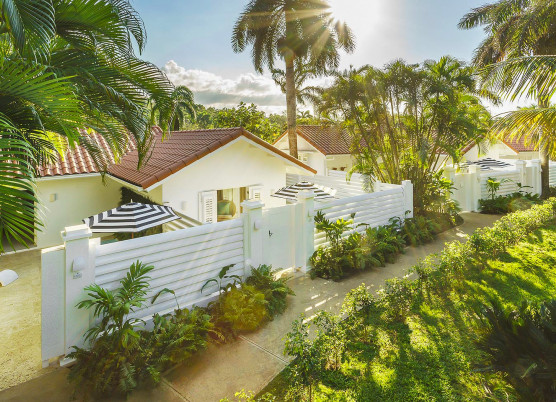 small yellow private villa buildings with individual yards with white fences