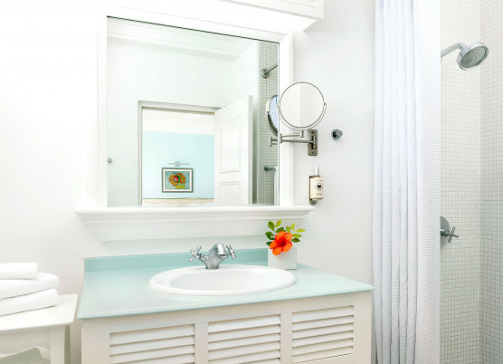 bathroom area with white cabinets, light blue countertops, shower, and white towels