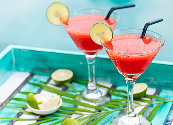 two strawberry and lime cocktails in martini glasses on a blue tray