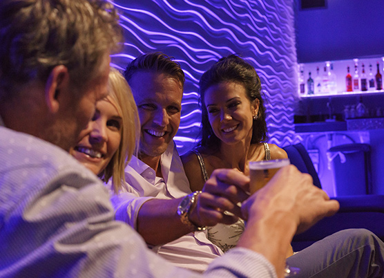 two couples sitting at a purple illuminated bar seating enjoying drinks
