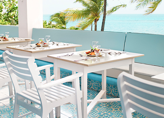 outdoor restaurant dining with white chairs and bench seating with a view of the ocean