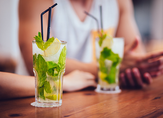 two mojito drinks sitting on a bar