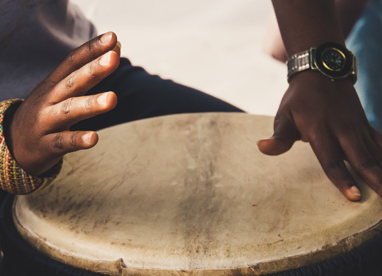 close up of a persons hands playing a wooden drum