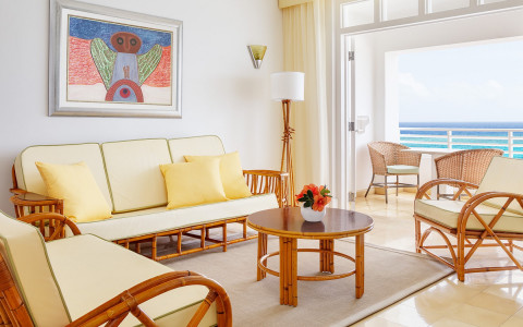 living room with light yellow cushions and a view of the balcony overlooking the ocean