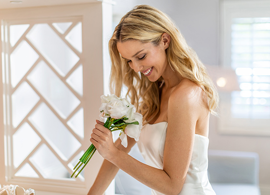 a bride smiling down at her bouquet of flowers