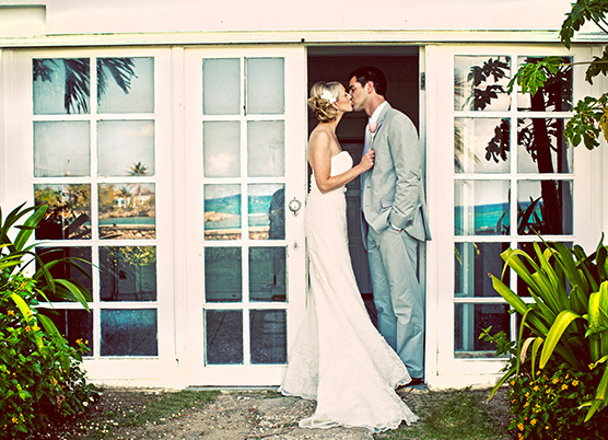 a bride and groom kiss standing in a door entrance