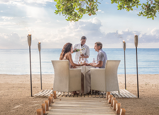 a couple having a private dinner on the beach
